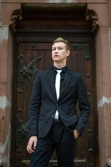 Handsome young man in trendy black suit and tie posing