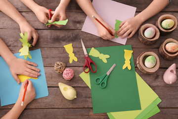 Little children making Easter decorations at table