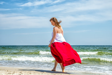 Beautiful girl in red dress by the sea.