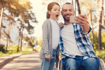 Moments to remember. Positive happy delighted man sitting in the wheelchair next to his daughter and smiling while taking a selfie