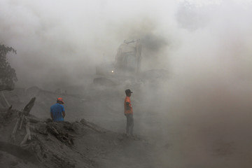 Residents are seen amidst ashes as heavy machinery removes ash from a road at an area affected by the eruption of the Fuego volcano at El Rodeo in Escuintla