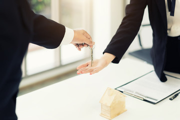 Real estate agent giving keys to apartment owner, buying selling property business. Close up of woman hand taking house key from realtor. Mortgage for purchasing flat, getting access to own home
