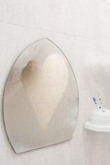 Bathroom misted mirror with heart shape drawn on it