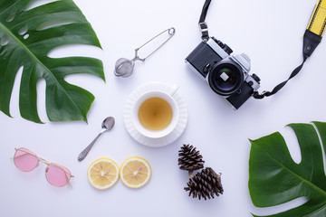 A glass of hot tea with fruit and leaves decorated on white background.