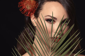 Portrait of young woman with beautiful professional makeup and palm leaf on dark background
