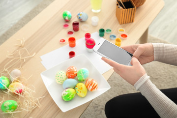 Young woman taking photo of painted Easter eggs at home