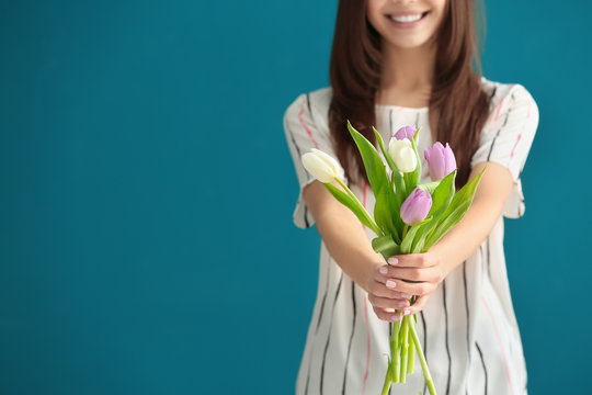 Beautiful young woman with bouquet of tulips on color background, closeup