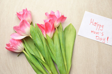 Beautiful tulips and handmade card for Mother's Day on light background