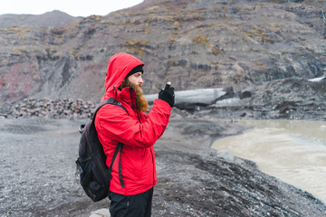 Man in warm clothes using smartphone in nature