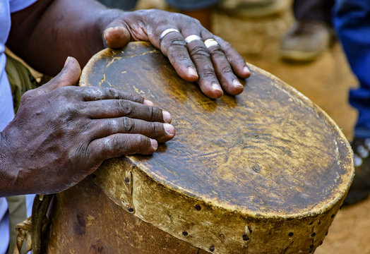 Percussionist playing a rudimentary atabaque during afro-brazilian cultural manifestation