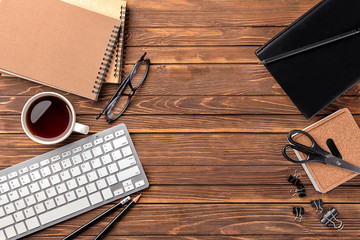 Computer keyboard, cup of coffee and stationery on wooden background, flat lay. Workplace table composition