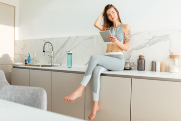 Pretty lady in sporty top and leggings sitting on kitchen table with tablet in hand and thoughtfully looking aside isolated