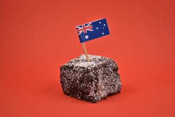 Lamington stock images. Lamington on a red background. Australian sweet delicacy. Important day. Lamington Day background. Australian cake with flag