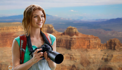 travel, tourism and photography concept - happy young woman with backpack and camera photographing over grand canyon national park background