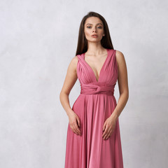 Beautiful long haired young woman dressed in stylish red bandeau maxi dress posing against white wall on background. Elegant brunette female model demonstrating evening outfit in studio.