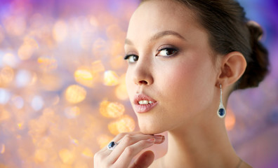 beauty, jewelry, people and luxury concept - close up of beautiful asian woman or bride with earring and finger ring over holidays lights background