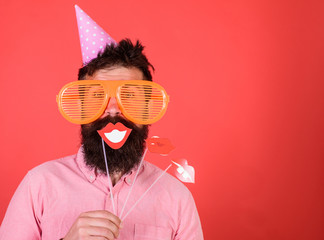 Guy in party hat celebrate, posing with photo props. Hipster in giant sunglasses celebrating. Man with beard on cheerful face holds smiling lips on sticks, red background. Emotional diversity concept