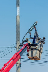 Electric technical in lift bucket during installation of metal p