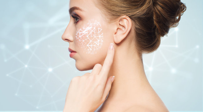 beauty, technology and people concept - beautiful young woman pointing finger to her skin over blue background with low poly shape projection on cheek