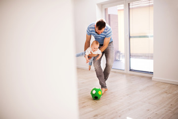Young father with a baby son at home playing with a ball.