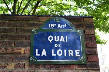 Quai de La Loire. Panneau devant un mir de briques et arbres.