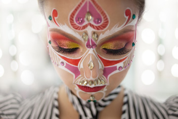 Young beautiful woman with skull makeup close her eyes
