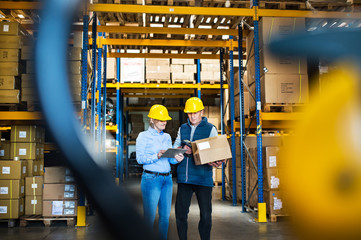 Senior managers or supervisors with tablet working in a warehouse, controlling stock.