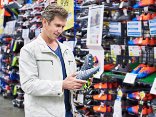 Man with football boots in sport store