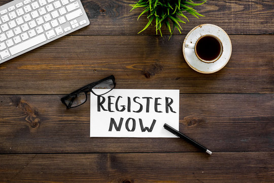 Membership concept. Template for registration. Register now hand lettering iconon word desk with glasses, coffee, plant on dark wooden background top view space for text