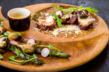 Grilled meat with vegetables in wooden plate on black background