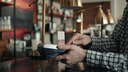 man paying bill through smartphone using NFC technology in cafe drink lemonade to go