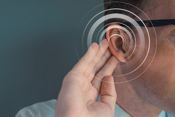 Man putting his hand on his ear. Deficiency hearing acousting problem. Empty space on the left
