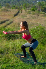 Young beautiful woman doing sport exercises with dumbbells