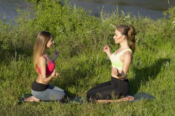 Two Young beautiful women doing peacefully yoga outdoors