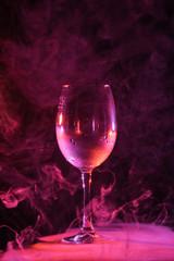 empty glass with pink smoke around on dark background
