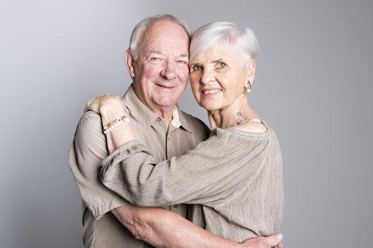 Senior couple posing on studio gray background