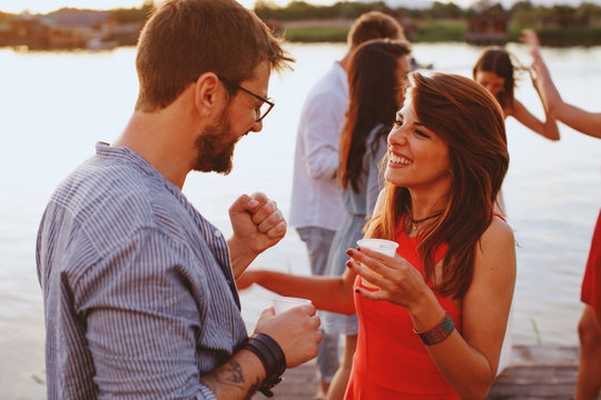 Man and woman flirting at party by the river