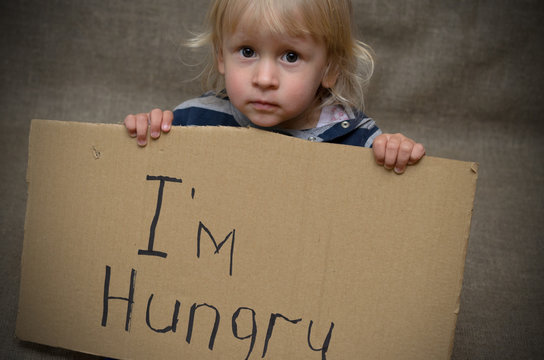 A hungry boy and a girl with a cardboard tablet with the inscription I'm hungry . The social problem.