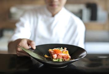Chef presenting a fish tartare in a black plate