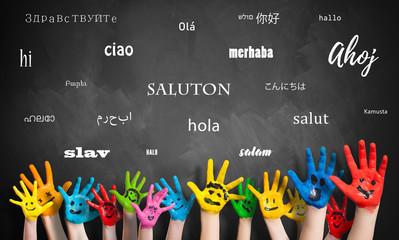 """Viele Kinderhände vor Wandtafel mit dem Wort """"Hallo"""" in vielen Sprachen"""