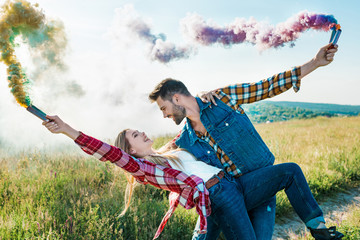 side view of man with colorful smoke bombs holding girlfriend back in rural field