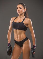Beautiful young sexy woman bodybuilder, in sportswear uses sports equipment, posing in front of the camera. Idyllic figure, beautiful waist, biceps, triceps. Motivation.