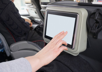 Woman touching blank lcd screen in the travel coach.