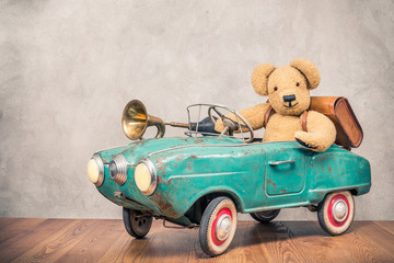 Teddy Bear and old leather school bag driving in rusty retro turquoise toy pedal car with classic brass klaxon in front concrete textured wall background. Vintage style filtered photo