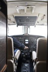 Faceless pilot flying modern aircraft