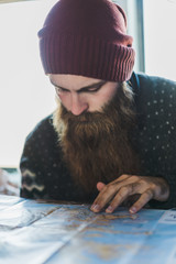 bearded man looking on map