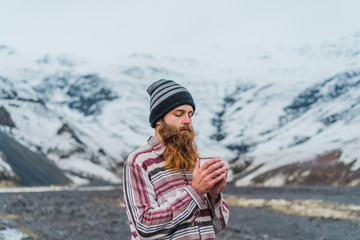 Man with mug standing on road in iceland