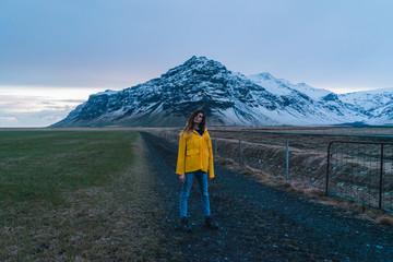 woman on Road towards snowy mountain