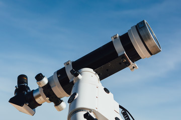 astronomical telescope tube, blue sky background