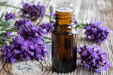 A bottle of essential oil with fresh blooming lavender Wall mural